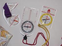Kuvassa erilaisia kompasseja: vasemmalla peukalokompassi, keskellä normaali levykompassi ja oikealla lapsille tarkoitettu starttikompassi