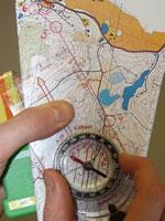2) Käännä kompassin neularasiaa siten, että sen pohjaviivat kulkevat samansuuntaisesti kartan koordinaattiviivojen kanssa. Varmista, että kompassin pohjoishaarukka osoittaa karttapohjoiseen (kartan yläreunaan).